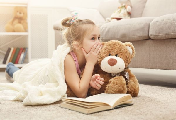 Girl with book and teddy bear