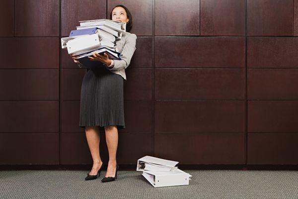 Women handing stack of papers