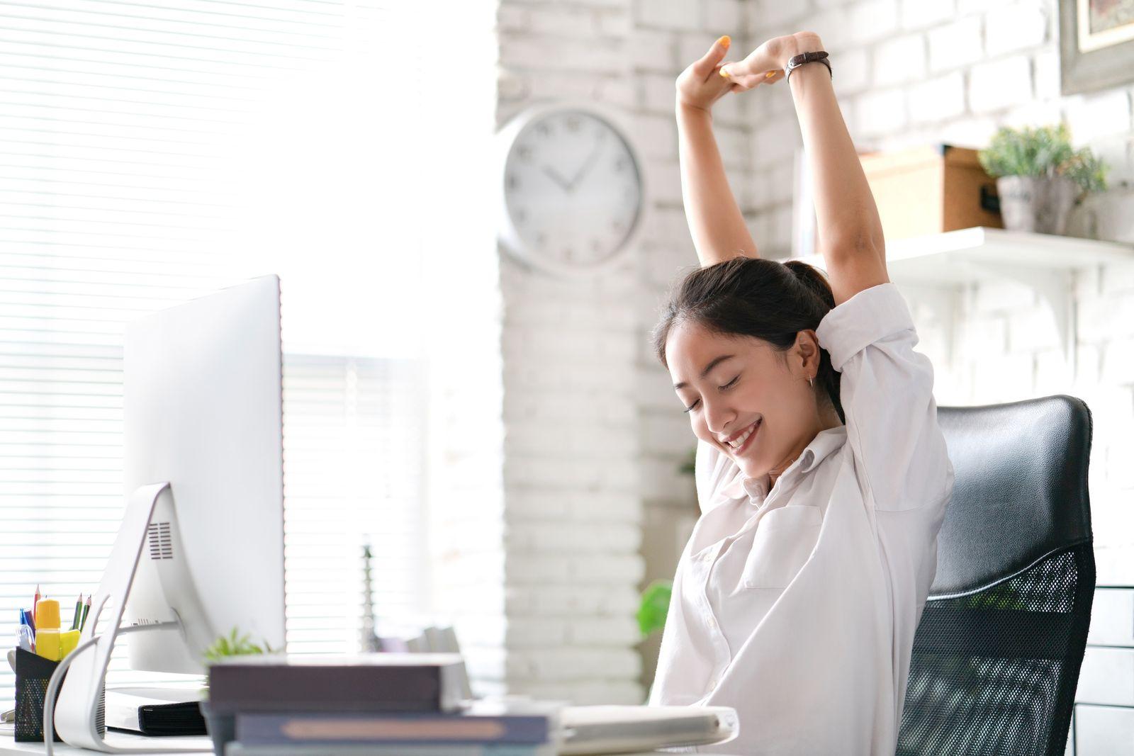 Femme qui s'étire dans son bureau