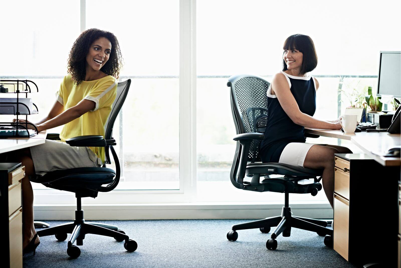 Female coworkers laughing and sitting in office chairs