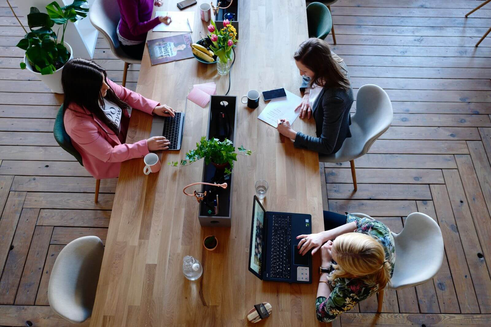 Female workers sitting at large office table