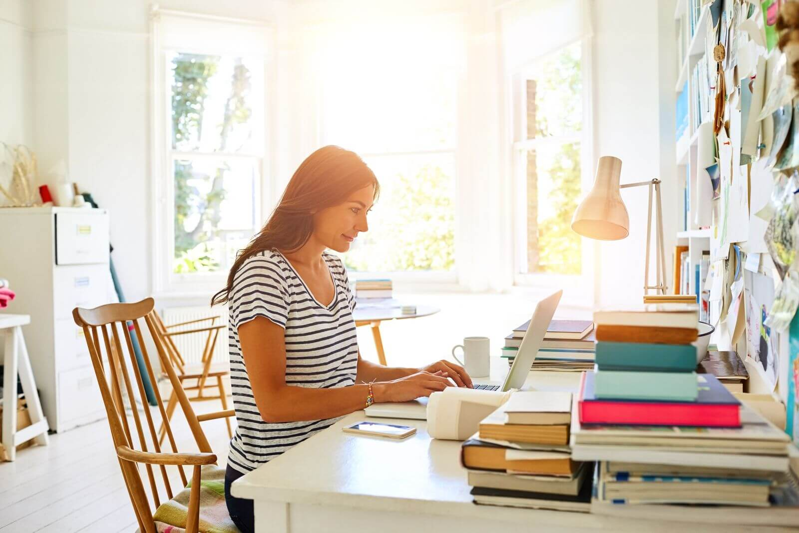 Woman working from home near window with sunlight