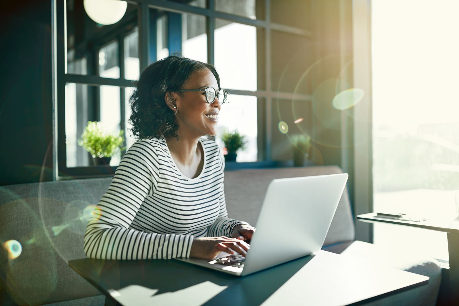 woman sitting at desk with sun coming in while she works from home