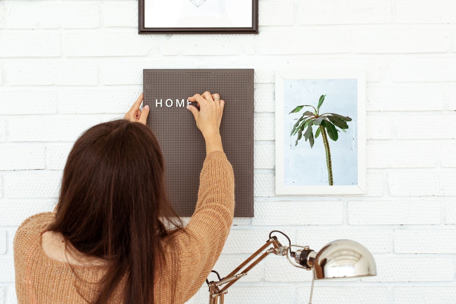 Woman decorating her home office with a letter board.