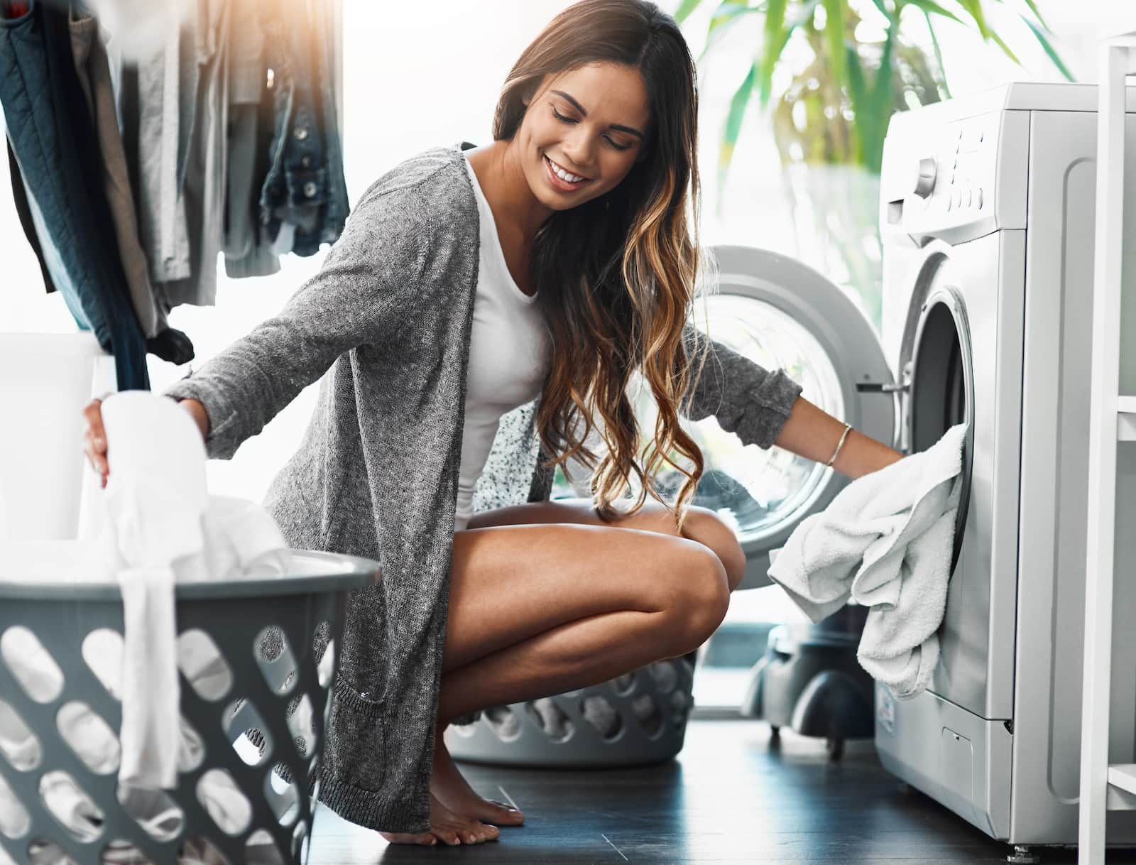 woman crouching next to dryer doing laundry