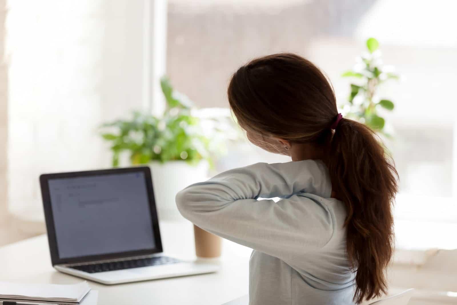 Femme qui s'étire le cou à l'ordinateur