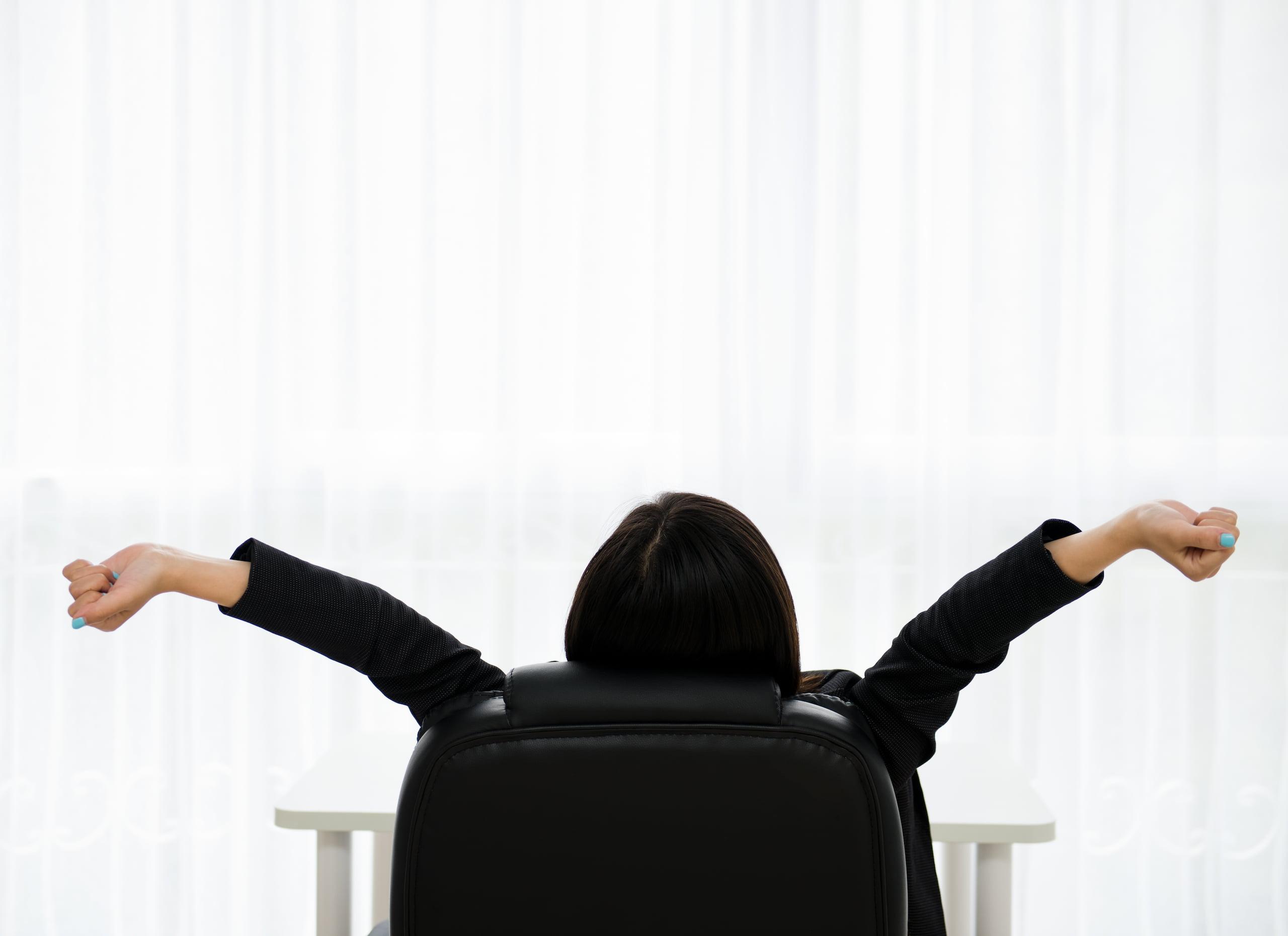 Femme qui s'étire sur sa chaise de bureau