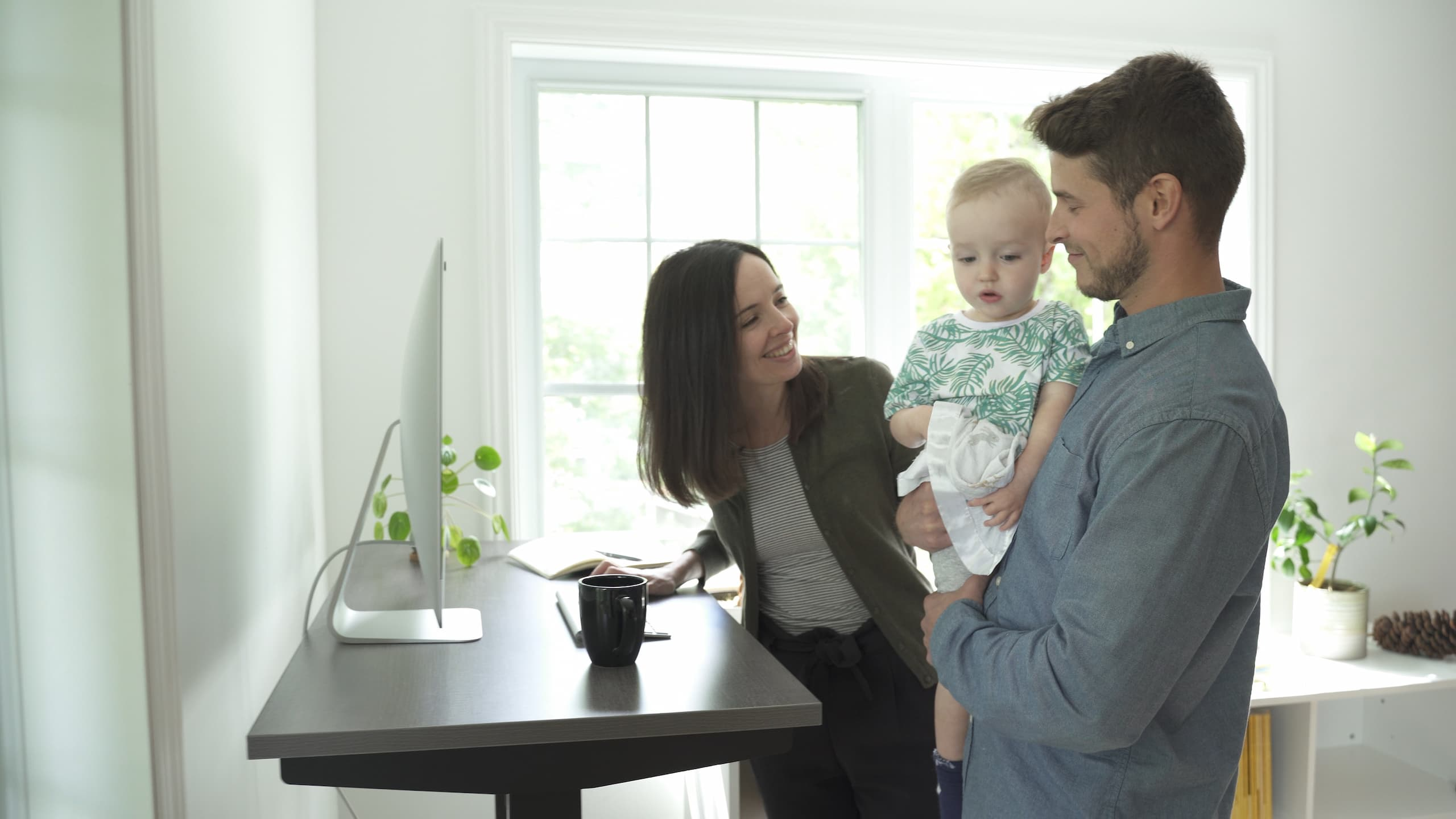 couple with baby next to standing desk