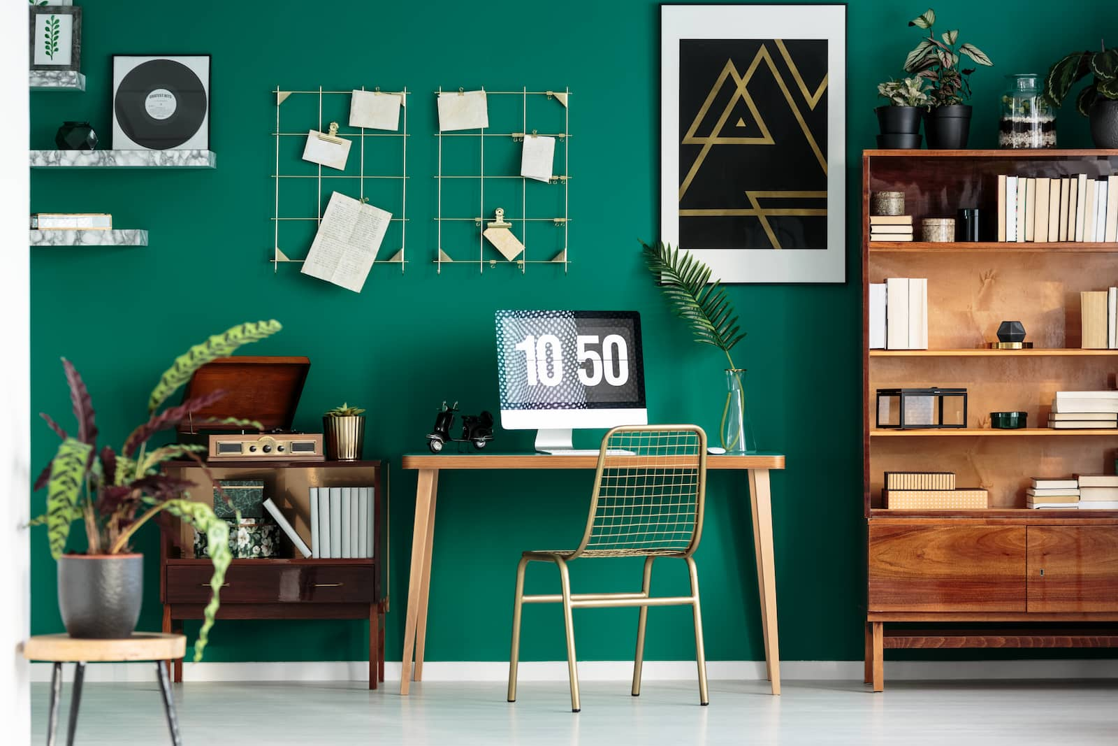 small desk next to green wall and decorations