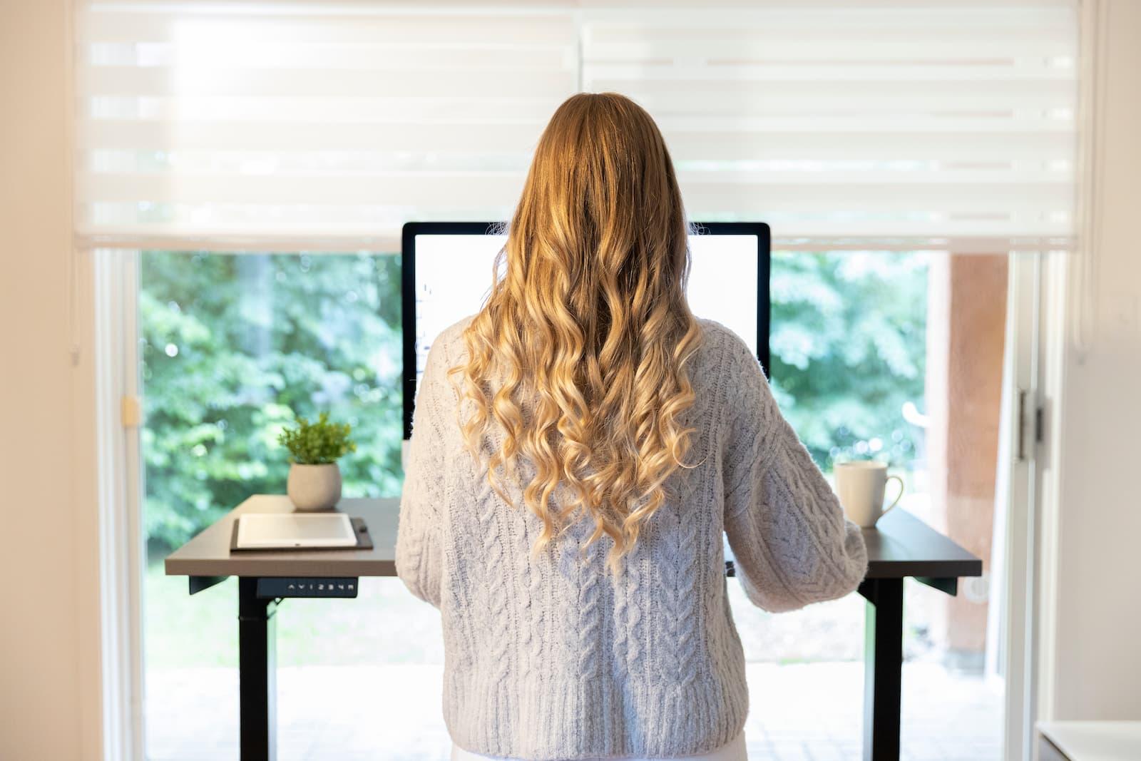 Jeune femme qui utilise le meilleur bureau assis-debout au Canada